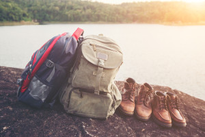 Backpacks and shoes with nature lake background.
